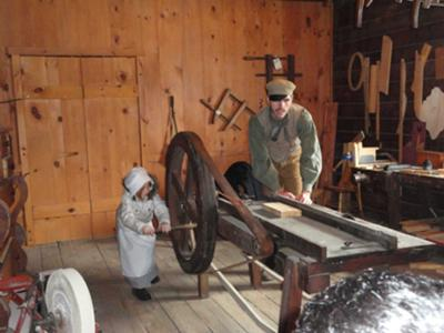 Katie operating the saw at the cabinet maker's shop
